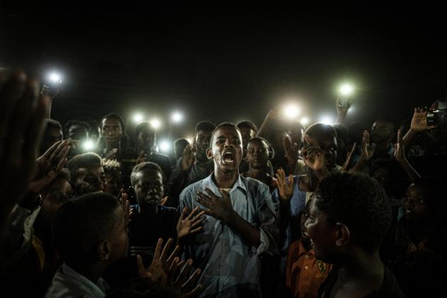 People chant slogans as a young man recites a poem, illuminated by mobile phones, at a protest in Khartoum, Sudan in June 2019.