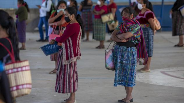 Women wearing face masks stand at a safe distance to help curb the spread of the new coronavirus, as they wait for food assigned to their children outside a school in Xesuj, Guatemala, where many residents depend on remittances, largely from the U.S. The