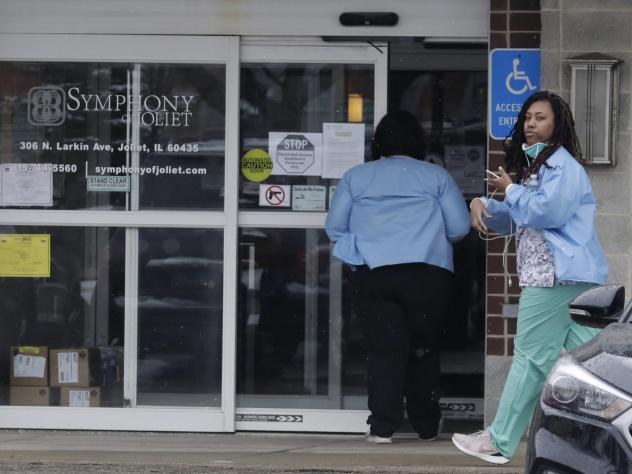 Employees of the Symphony of Joliet nursing home in Joliet, Ill., go to work last Friday. At least 21 people, including two staff members, have died of COVID-19 at the facility.