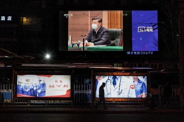 A large screen in the street shows Chinese leader Xi Jinping wearing a protective mask during his visit to Wuhan, China, earlier in the day, on CCTV's evening newscast in March in Beijing, China.