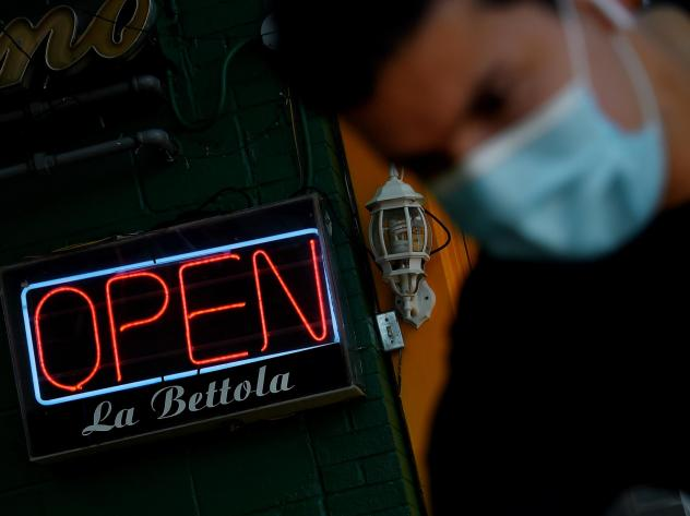 On Wednesday, an employee cleans the entrance of a restaurant in the Crystal City neighborhood of Arlington, Va., as restaurants and businesses try to adapt to the ever-changing situation amid the coronavirus pandemic.