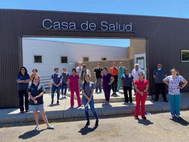 Casa de Salud clinicians, staff and health apprentices socially distance outside their New Mexico clinic. The facility is one of many social safety net clinics that haven't yet received pandemic-related funding and are now on the brink financially.