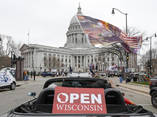 People in cars participate in a protest against the coronavirus shutdown in front of the state capitol in Madison, Wisc., on April 24, 2020.