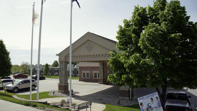 A flag flies on the grounds of the Life Care Center nursing and rehabilitation facility in Elkhorn, Neb., where a large number of staff and residents tested positive for COVID-19.