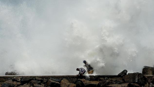 Two men duck for cover as waves generated by Cyclone Amphan smash against a breakwater Tuesday in Chennai, India. Farther north along India's east coast, near the country's border with Bangladesh, officials are struggling to evacuate areas in the storm's