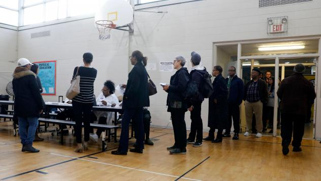 People stand in line at a Detroit polling place during Michigan's March 10 presidential primary. Because of the pandemic, the state's top election official is sending absentee ballot applications to every registered voter for August and November election