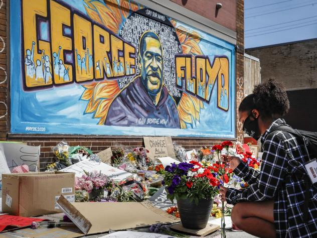Malaysia Hammond places flowers at a memorial mural for George Floyd in Minneapolis on Sunday. Police brutality has sparked days of civil unrest. But the sparks have landed in a tinderbox built over decades of economic inequality, now exacerbated by the