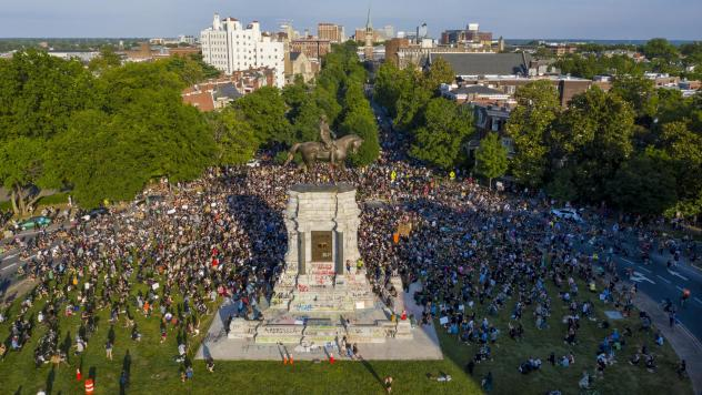 """A large group of protesters gathered around the statue of Confederate Gen. Robert E. Lee, on Tuesday in Richmond, Va. The crowd protesting police brutality chanted, """"Tear it down."""""""