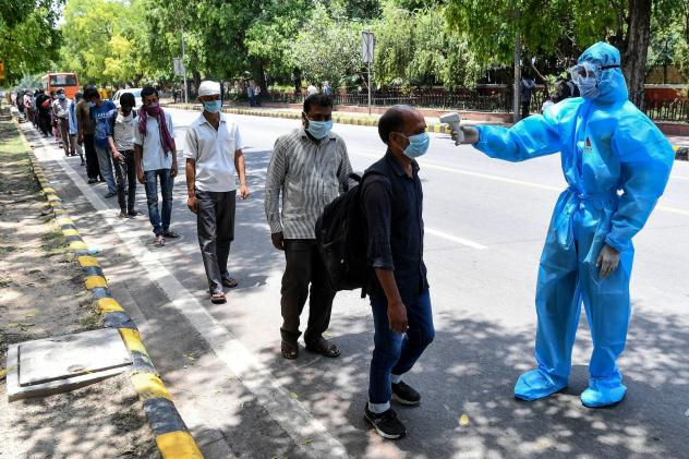 A volunteer wearing a protective suit checks the body temperature of homeless people standing in line to get free lunch packets on the roadside after the government eased a nationwide lockdown, in New Delhi, late last month.