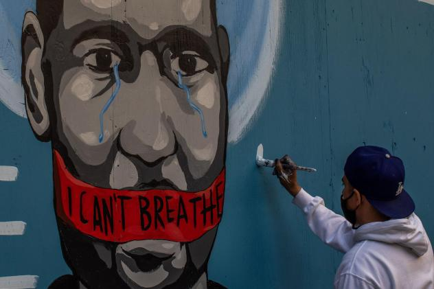The artist Celos paints a mural in downtown Los Angeles on May 30, 2020 in protest against the killing of George Floyd by police in Minneapolis.