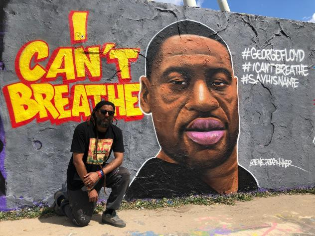 "Graffiti artist Eme Freethinker kneels in front of his portrait of George Floyd, which he painted on one of the last remaining sections of the Berlin Wall. ""I remember when I came in [to paint it], some guy told me, 'You have to do it with the police ove"
