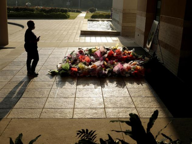 A woman stops to photograph a memorial for George Floyd at The Fountain of Praise church on Tuesday in Houston.