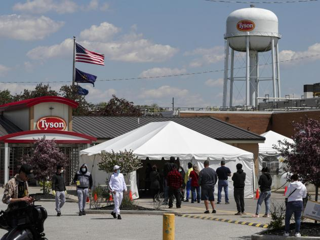 Workers line up to enter a Tyson Foods pork processing plant last month in Logansport, Ind. Some of the worst workplace coronavirus outbreaks have been in the meatpacking industry. Safety advocates say the companies still aren't doing enough to protect w