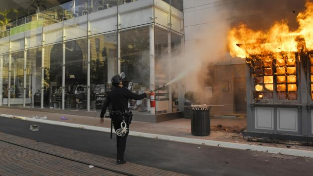 An officer tries to put out a fire at a police kiosk at The Grove shopping center in Los Angeles during a protest last month over the death of George Floyd.