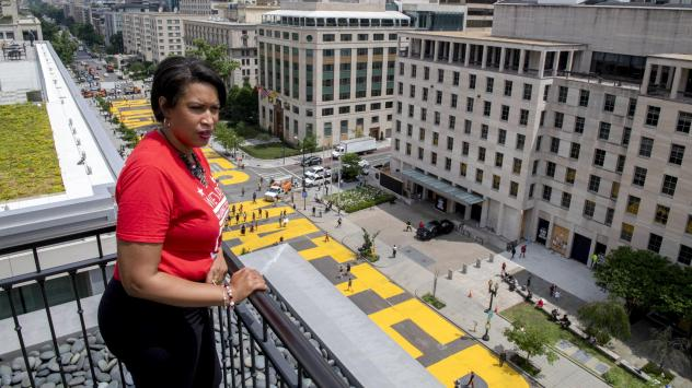 """Mayor Muriel Bowser stands on the rooftop of the Hay-Adams Hotel near the White House and looks out at the words """"Black Lives Matter"""" that have been painted in bright yellow letters on the street."""
