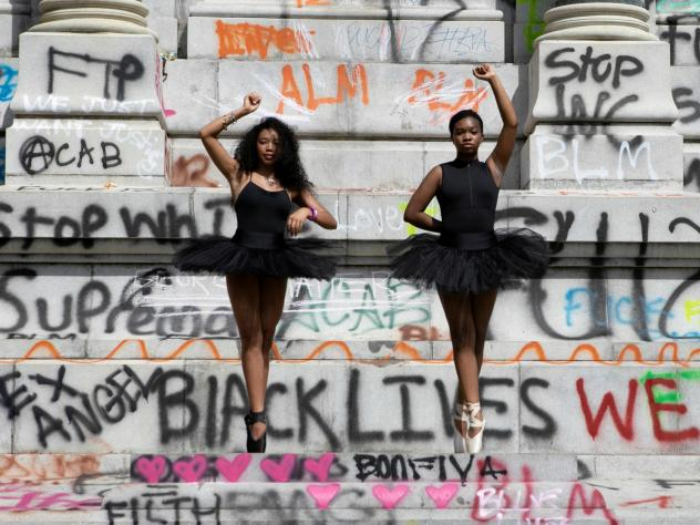 Ballerinas Kennedy George, 14, and Ava Holloway, 14, pose in front of a monument of Confederate general Robert E. Lee after Virginia Governor Ralph Northam ordered its removal after widespread civil unrest following the death in Minneapolis police custod