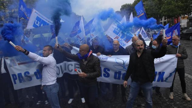 """French police unionists fire blue flares as they demonstrate with a banner reading"""" No police, no peace"""" down the Champs-Élysées in Paris on Friday."""