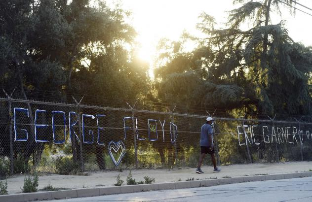 "A walker passes by the names of George Floyd and Eric Garner spelled out in fabric at the art installation ""Say Their Names: Silver Lake Memorial"" at the Silver Lake Reservoir, on June 9, in Los Angeles. There has been a recent push for a nationwide ban"