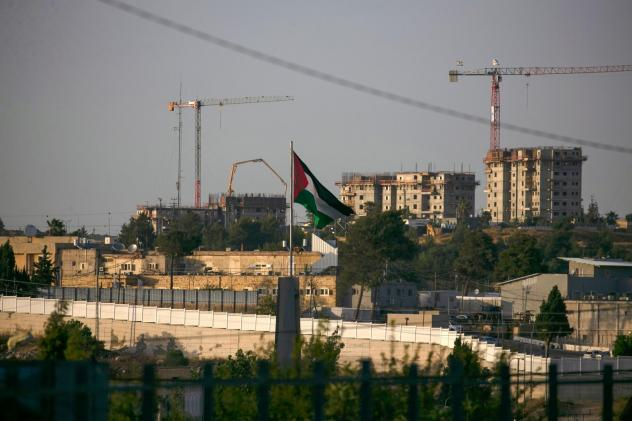A Palestinian flag waves at the northern entrance to the city of Ramallah in the occupied West Bank as construction works take place in the Israeli settlement of Beit El in the background. Israel intends to annex West Bank settlements and the Jordan Vall