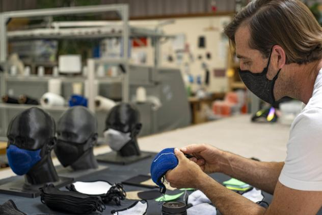 Billy Smith counts rows in the knit structure of a mask to assure specifications for fit and sizing meet company standards.