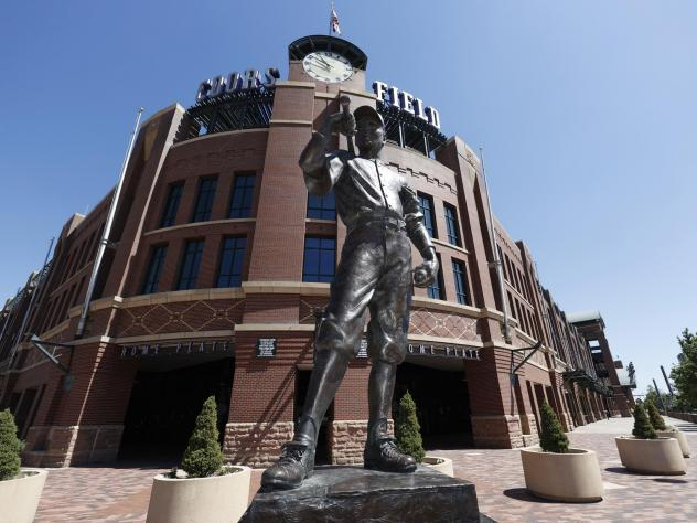 A bronze baseball player stands outside Coors Field in Denver, one of the stadiums idled during the coronavirus outbreak. The league and players association have agreed to  league is waiting for the players' union to respond to whether it will agree to p