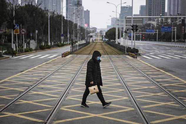 A resident walks across an empty track on Feb. 7 in Wuhan, China. Wuhan residents lived through the start of the coronavirus pandemic, which has claimed hundreds of thousands of lives around the world.