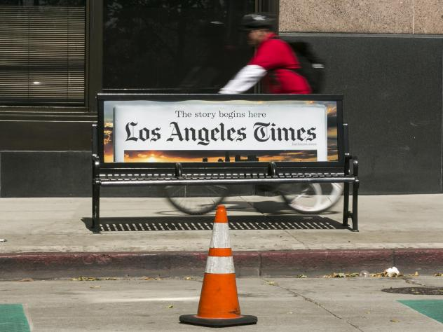 A cyclist rides on the sidewalk past a <em>Los Angeles Times</em> advertisement in downtown Los Angeles. The newspaper is being sued by employees alleging pay discrimination.