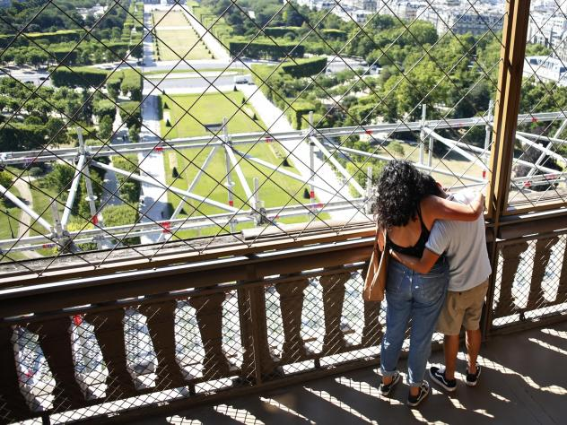 A couple take in the view as they visit the Eiffel Tower on Thursday. Paris' iconic tower is reopening after the coronavirus forced the longest closure since World War II.
