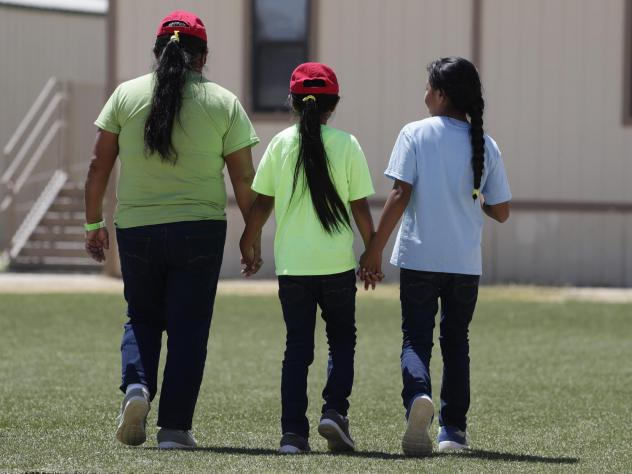 Immigrants seeking asylum hold hands as they leave a cafeteria at the ICE South Texas Family Residential Center. Independent inspectors told the judge that COVID-19 tests at the centers and the infection rates in the counties where the Texas facilities a