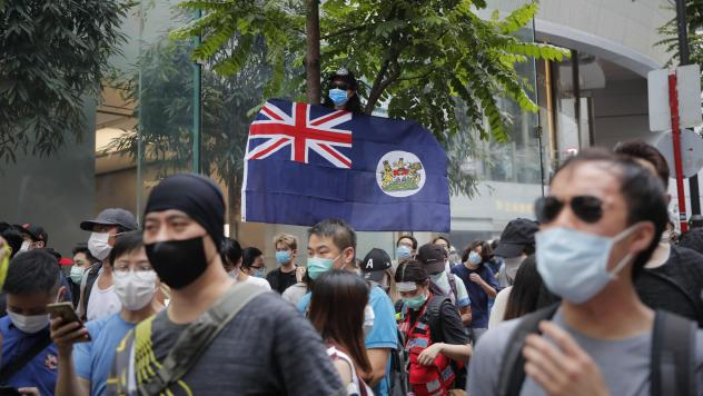 A man displays the Hong Kong colonial flag Wednesday, the anniversary of the city's handover to China from Britain in 1997. The gesture could be prosecuted under Bejing's new national security law, which it imposed on Hong Kong.
