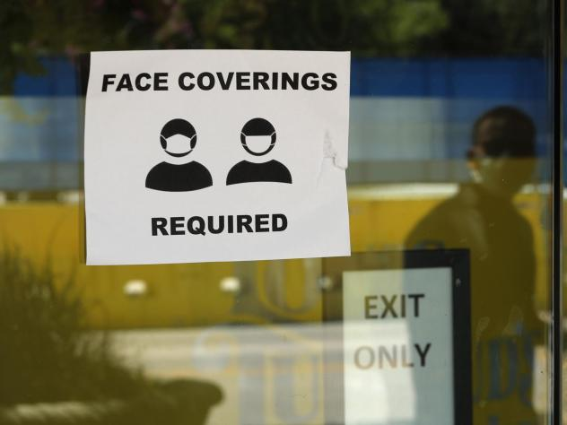 A business in San Antonio posts a reminder about face masks. The city is one of a growing number of localities and states mandating that face coverings be worn in public.
