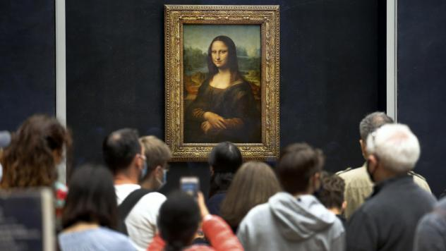 Visitors wearing face masks wait to see the <em>Mona Lisa</em> at the Louvre Museum on Monday. The most visited museum in the world reopened to the public after closing in March.