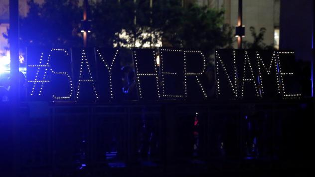 "Protesters hold up a lighted sign reading ""#sayhername"" during a July 2015 vigil for Sandra Bland in Chicago. Bland died in a Texas jail after a traffic stop escalated into a physical confrontation. Authorities said Bland hanged herself, a finding her fa"