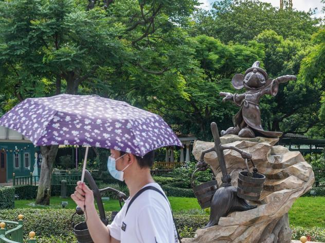 A visitor wearing a protective mask walking past a statue of Mickey Mouse at the Disneyland Resort in Hong Kong on the day it initially reopened, June 18. The amusement park will close again on Wednesday.