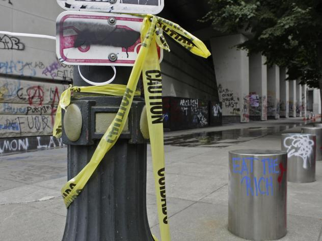 Graffiti from recent demonstrations covers an area outside the Mark O. Hatfield Federal Courthouse in Portland on July 8. Protesters are facing off not just against the Portland police but a group of federal agents.