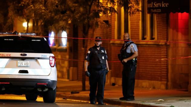 Chicago Police Department officers stand in front of Rhodes Funeral Services as they investigate the scene of a shooting Tuesday night. Gun violence outside a funeral left at least 15 people wounded.