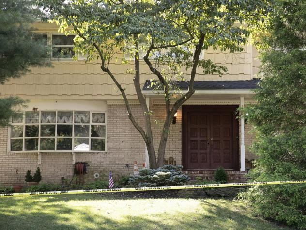 Crime scene tape surrounds the home of U.S. District Judge Esther Salas on Monday in North Brunswick, N.J. A gunman posing as a delivery person shot and killed Salas' 20-year-old son and wounded her husband Sunday evening  before fleeing, according to of