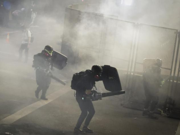 Demonstrators use leaf blowers to try to blow back tear gas launched by federal officers during a Black Lives Matter protest at the Mark O. Hatfield United States Courthouse on Sunday in Portland, Ore.