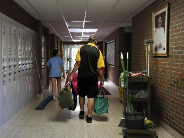 Cesa Pusateri, 12, and her grandfather, Timothy Waxenfelter, principal of Quigley Catholic High School, leave with his collection of speech and debate books after the closure of the school in Baden, Pa., on June 8, 2020. According to the National Catholi