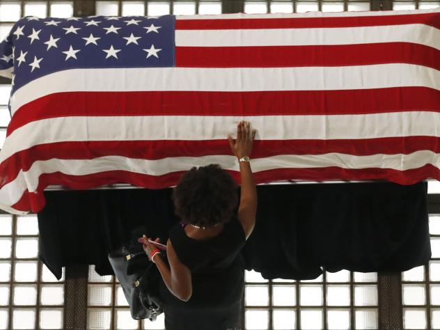 A mourner pauses by the casket of Rep. John Lewis lying in repose at the Georgia state Capitol on Wednesday in Atlanta. Lewis, who carried the struggle against racial discrimination from Southern battlegrounds of the 1960s to the halls of Congress, died