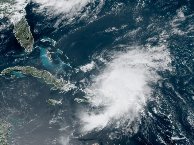 A satellite image from Thursday morning shows Tropical Storm Isaias looming over Puerto Rico and the Dominican Republic. The storm is predicted to drench Florida over the weekend.