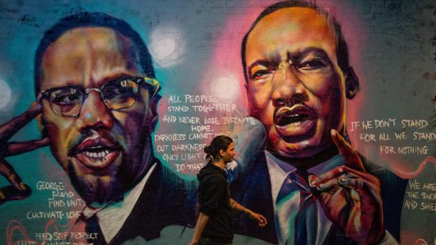A man walks past a mural of Malcom X and Martin Luther King Jr. in London.