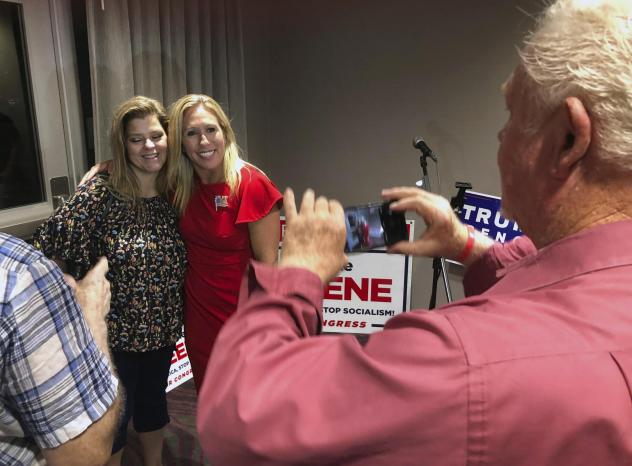 Marjorie Taylor Greene (right) is likely to bring a far-right conspiracy theory to the House of Representatives next year.
