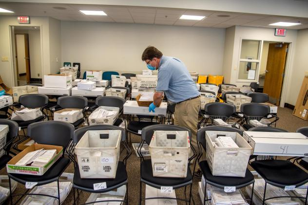 Election official Jim Fortner places a crate of sorted absentee ballots with others from the same ward at the Madison, Wis., City-County Building on Aug. 5, 2020. Delays and failure to deliver absentee ballots in Wisconsin and other key swing states have