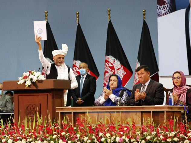 Afghan President Ashraf Ghani holds up a resolution on the last day of a traditional council known as a Loya Jirga, in Kabul, Afghanistan, Aug. 9. The council concluded with hundreds of delegates agreeing to free 400 Taliban members, paving the way for a
