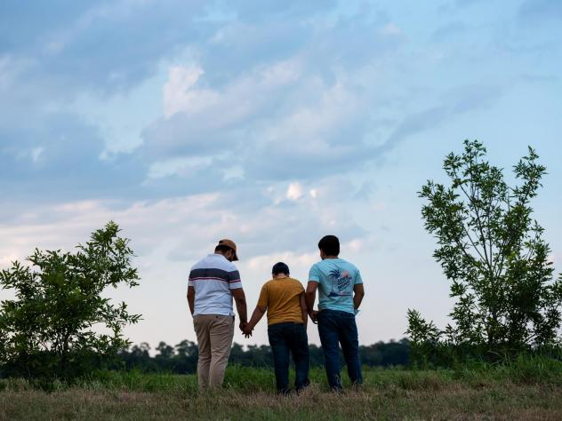 Honduran migrants, Ricardo Sr., (left), his son Ricardo Jr., 13, and his cousin Jorge, 16, walk near their home in Texas. When the two teenage boys crossed the border illegally into Texas last month, they turned themselves in to the Border Patrol. They w