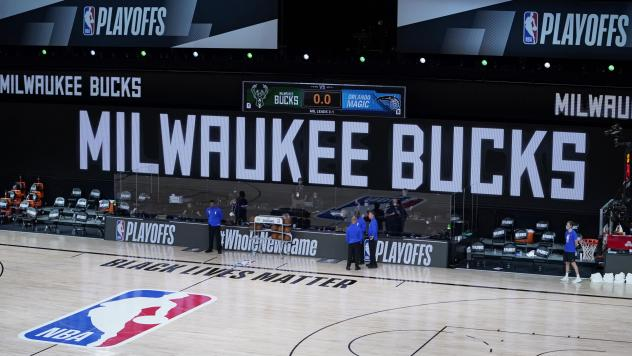 Officials stand beside an empty court at the scheduled start of an NBA basketball playoff game between the Milwaukee Bucks and the Orlando Magic, Wednesday in Lake Buena Vista, Fla. The Bucks didn't take the floor in protest against racial injustice and