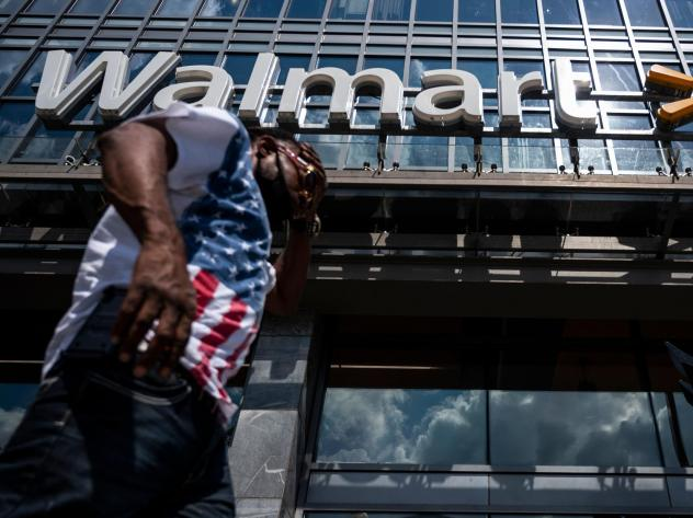 """A man walks past a Walmart store in Washington, D.C. on July 15. Walmart said it was """"confident"""" that its joint deal with Microsoft would satisfy both TikTok users and U.S. government regulators."""