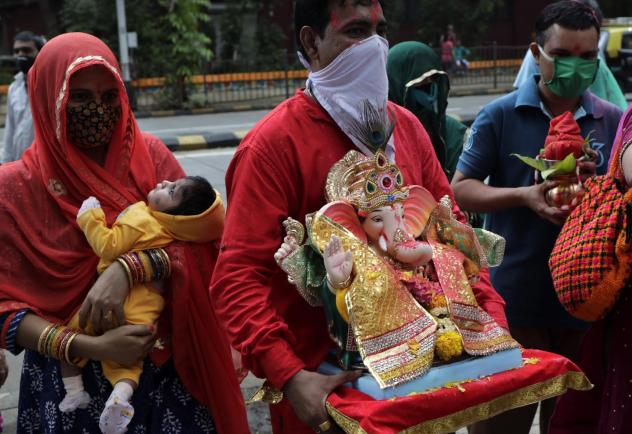 Devotees prepare to immerse in an artificial pond an idol of elephant-headed Hindu god Ganesh in Mumbai, India, Aug. 23. India's coronavirus caseload topped 3 million that day, with the country leading the world in new daily infections.