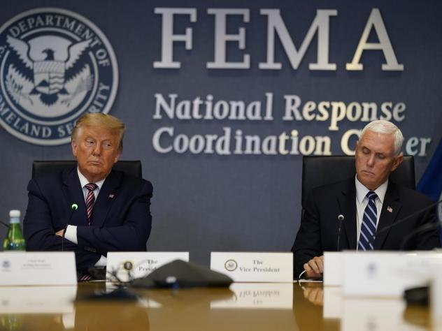 President Donald Trump and Vice President Mike Pence listen during a Hurricane Laura briefing at FEMA headquarters in Washington.